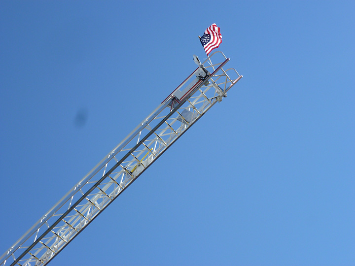 Photo with US flag at the top of a ladder for Cecil County Fire Expo.