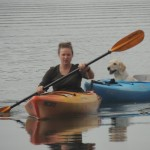 Lucy the Golden Retriever sitting in kayak with owner.